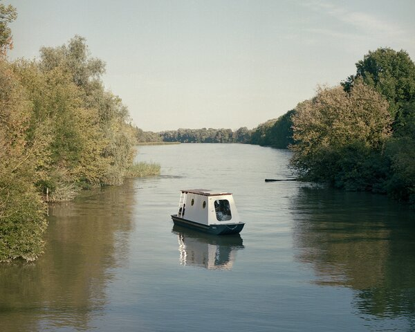 The tiny houseboat, named Sneci, is crafted primarily from wood and aluminum.