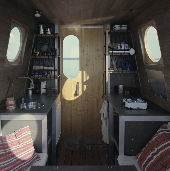 The boat's cabin is split into two distinct areas—the kitchen and the dining area/bedroom.