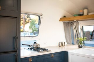 The wraparound kitchen, located at the front of the Airstream, includes a Miele 2-burner cooktop, a Dometic RV fridge, and a split ceramic farmhouse apron sink.