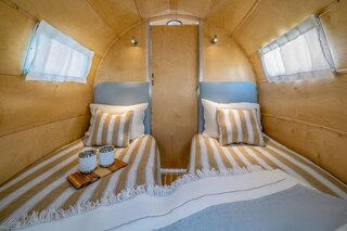 The trailer sleeps four people, two in the rear bedroom and two in the main living space.
