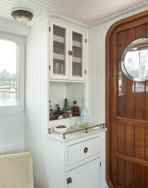 Design elements like white beadboard and brass hardware give the tugboat's interior a classic nautical vibe.
