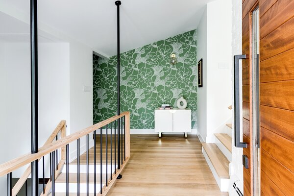 In the foyer, an accent wall covered in Farrow & Ball Helleborus wallpaper sets the tone for the home's retro-meets-contemporary aesthetic.