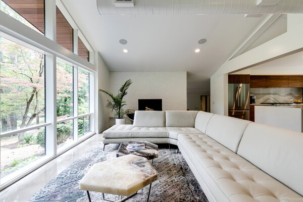 Taking cues from indoor/outdoor houses in Palm Springs, Ron sought to bring finishes from the outside in. The large brick fireplace in the living room is painted the same shade as the brick exterior, Sherwin-Williams Pure White.