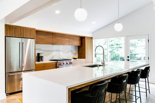 Custom walnut cabinetry designed by Michael Weidner at Radhaus Kabinett Co. are framed by a Cambria Brittanicca Warm backsplash and topped with Q Premium Natural Quartz and Calico white quartz countertops.