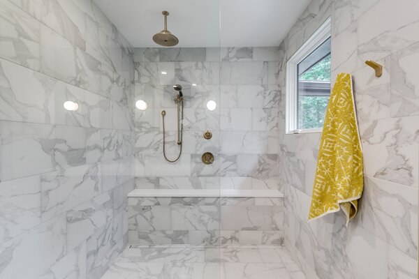 Dimarmi Bianco porcelain tile extends from the primary bath's floor into the shower.