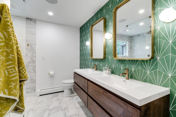 To pay homage to the home's era, the couple chose a midcentury-inspired Pacific Green Starburst III tile from the Cement Tile Shop to go behind the Moreno Bath MOB rosewood vanity. Hudson Valley Lighting fixtures and CB2 mirrors add some retro bling to the bath.