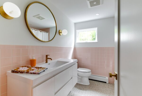 The guest bath has a retro feel with Clé Tile's Forage white terrazzo, New York Tile Company's 4x4 pink tile, a Moreno Bath MOB high-gloss white vanity, and light fixtures and a mirror from West Elm.