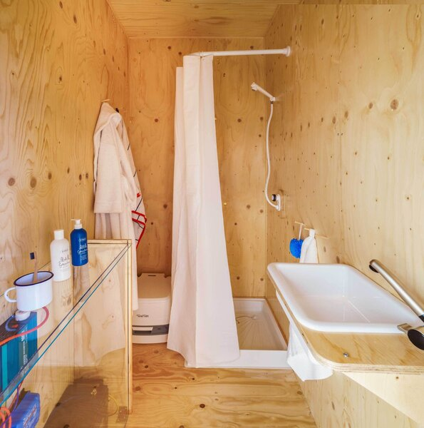 The small bathroom is fully equipped with a shower, sink, and composting toilet.