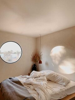 A round window casts a lunar-like glow above the bed in one of the suites.