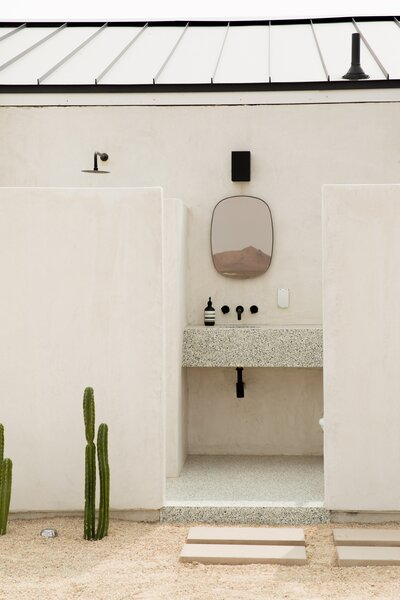 The home's exterior features a smooth, white stucco. An open-air bathroom features a sink constructed using a custom terrazzo made by Mila.