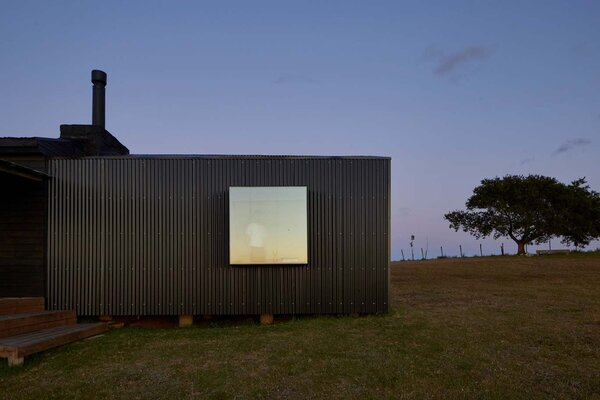 The bedroom additions are clad in black corrugated sheet metal.
