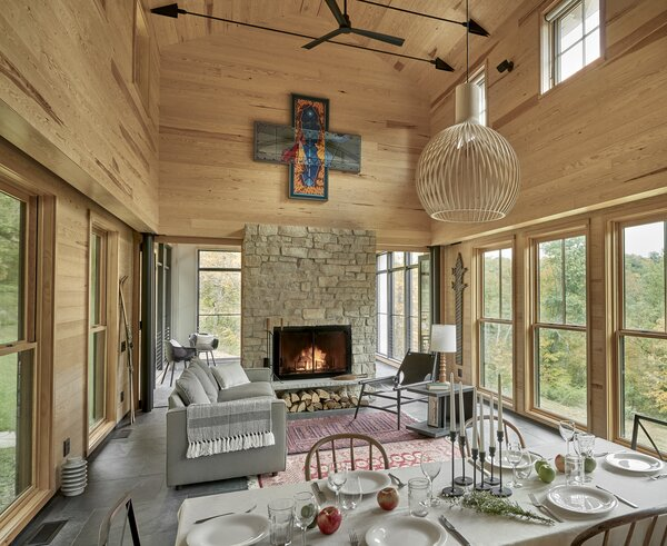 Limestone used on the exterior was employed inside as well, creating material continuity on the interior and exterior. Minimalistic bi-folding doors separate the screened porch from the voluminous pine-clad family room.