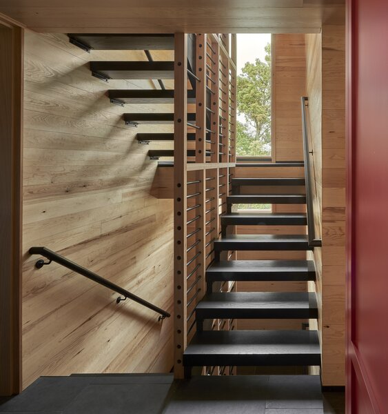 """""""It's very similar to what you'd see for corn storage,"""" the homeowner says of the custom designed stairwell screen. On the landing, a long vertical window frames a picturesque view of the property. As a passageway that you would typically walk through quickly, the design details in the stairwell create an experience where you instead stop and linger."""