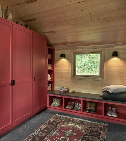 After entering the front door, tomato red shaker-style cabinetry in the mudroom sets the tone for a warm family home.