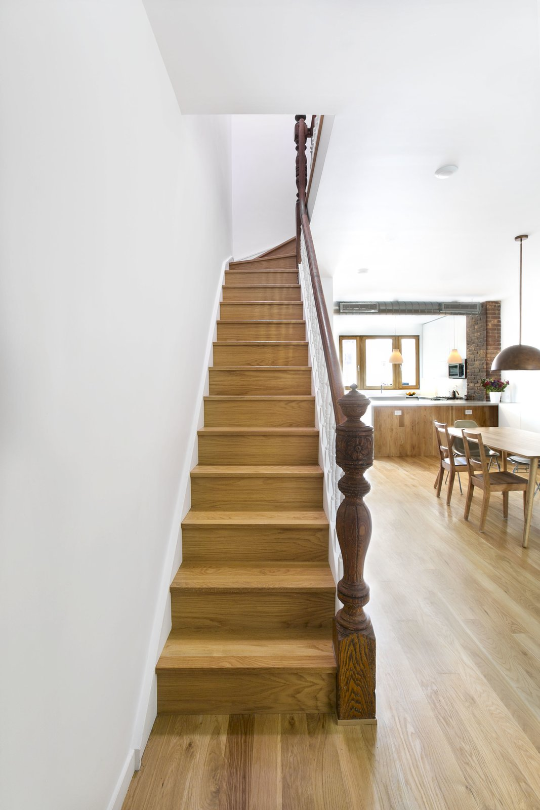 Staircase, Wood Railing, and Wood Tread Stairs from parlor floor to second floor, with original railing.  Sunset Park Row House