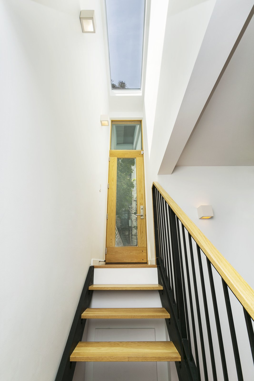 Staircase, Wood Tread, Metal Railing, Metal Tread, and Wood Railing Exit from basement apartment to backyard.   Sunset Park Row House