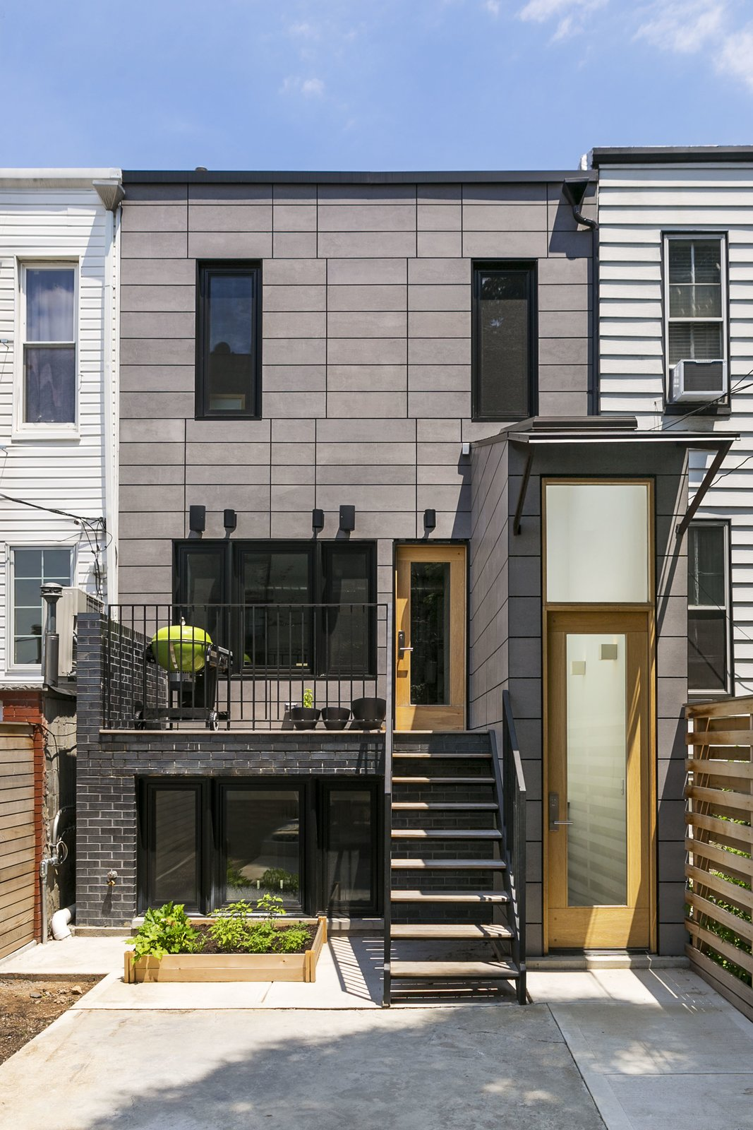 Outdoor, Back Yard, Hardscapes, Small Patio, Porch, Deck, Wood Patio, Porch, Deck, and Vertical Fences, Wall The rear facade.  Sunset Park Row House