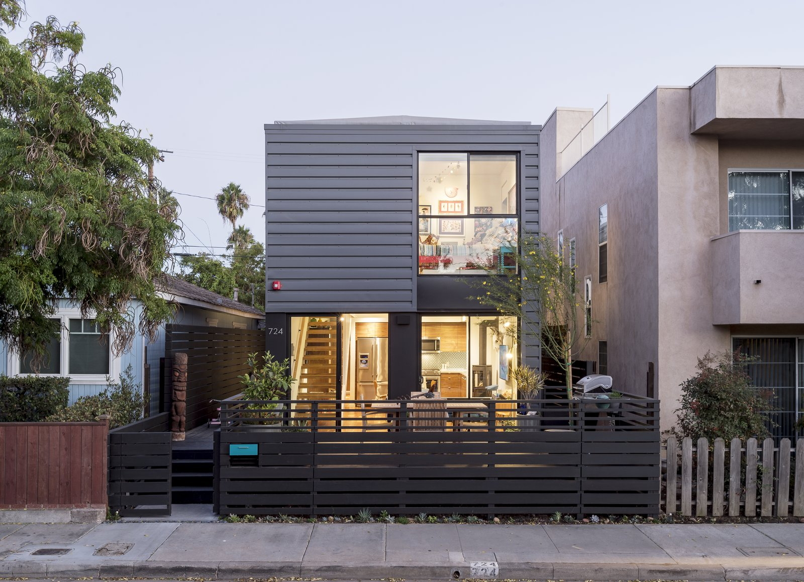 Outdoor, Vertical Fences, Wall, Front Yard, Shrubs, Large Patio, Porch, Deck, Trees, Hardscapes, Wood Patio, Porch, Deck, Decking Patio, Porch, Deck, and Wood Fences, Wall The exterior of Connect 4L 1,600 sf 3 bed 3 bath 2 story modern prefab.  Best Photos from Santa Monica Connect 4L