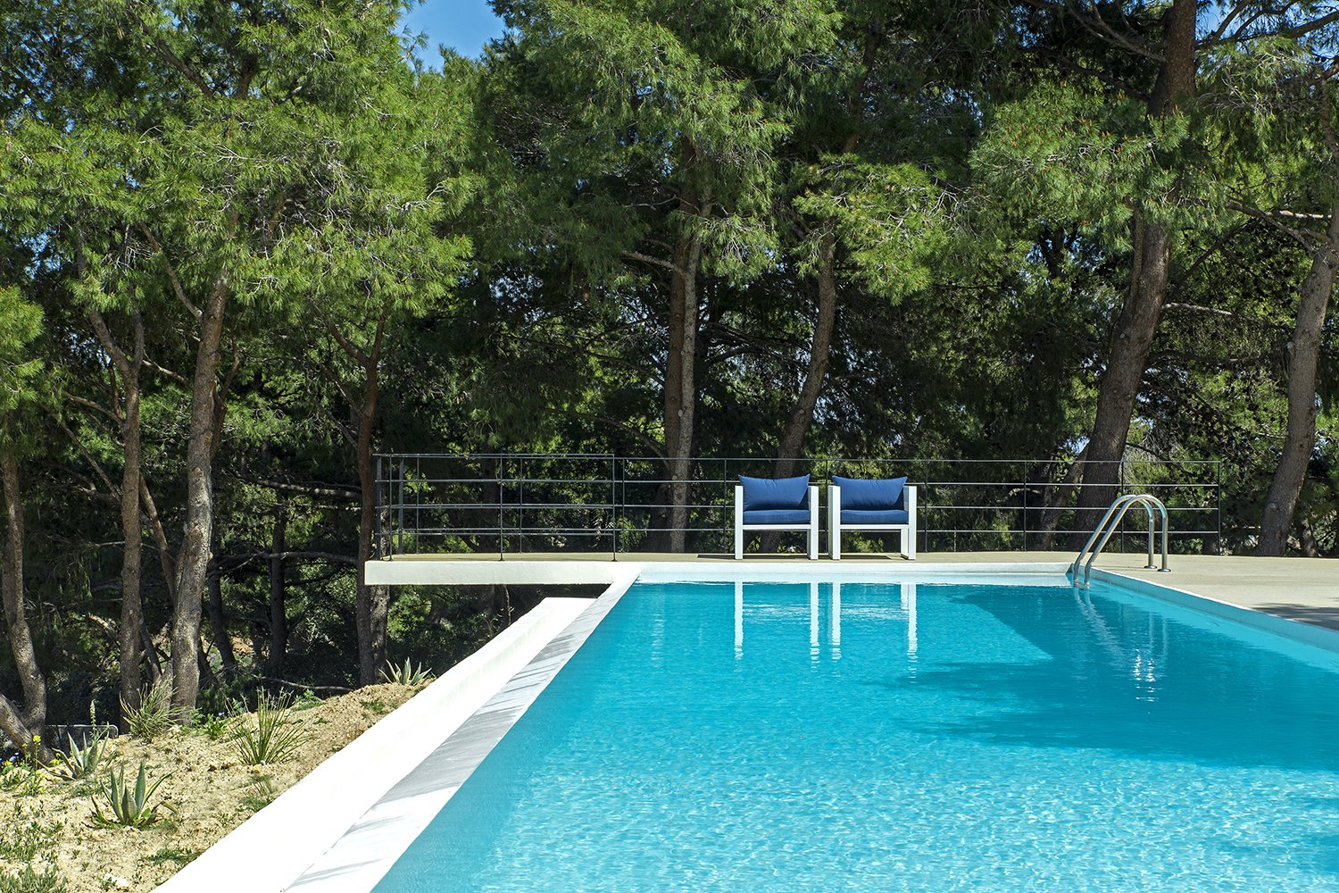 The longitudinal swimming pool reenacts a narrow stream coming through a canyon at a lower level Tagged: Outdoor, Infinity Pools, Tubs, Shower, Lap Pools, Tubs, Shower, Large Patio, Porch, Deck, Metal Fences, Wall, and Trees.  The Wedge House