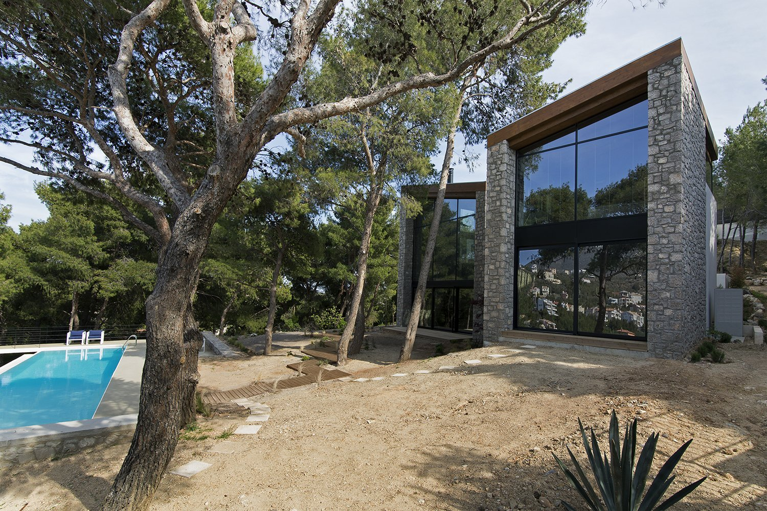 Exterior, Stone Siding Material, Shingles Roof Material, House Building Type, and Wood Siding Material Both facades completely open up through large glazing surfaces to the view of the pines trees and the hills beyond  The Wedge House