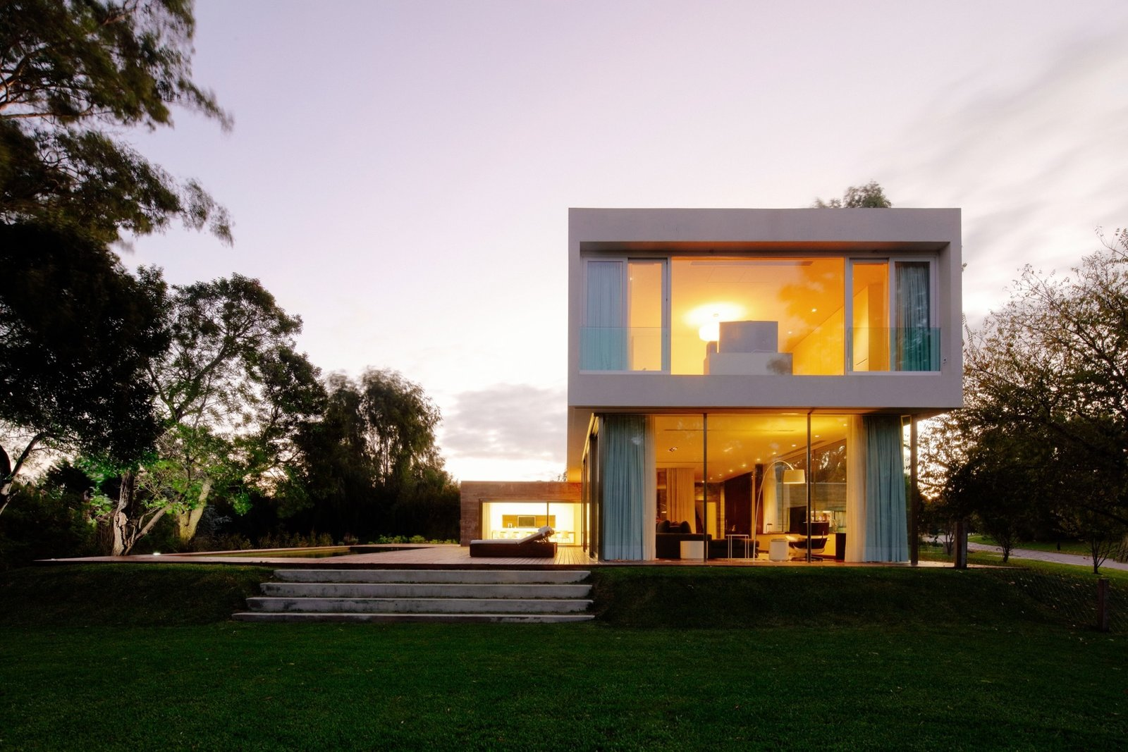 Outdoor, Large Patio, Porch, Deck, Grass, Back Yard, Trees, and Wood Patio, Porch, Deck Side view of the House at Los Cisnes at dawn. Concrete, Glass, Wood.  House at Los Cisnes by Esteban Fallone