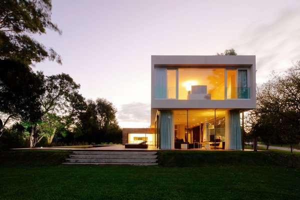 Side view of the House at Los Cisnes at dawn. Concrete, Glass, Wood.