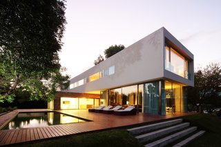 Wooden deck of the House at Los Cisnes at dawn. Concrete, Glass, Wood.