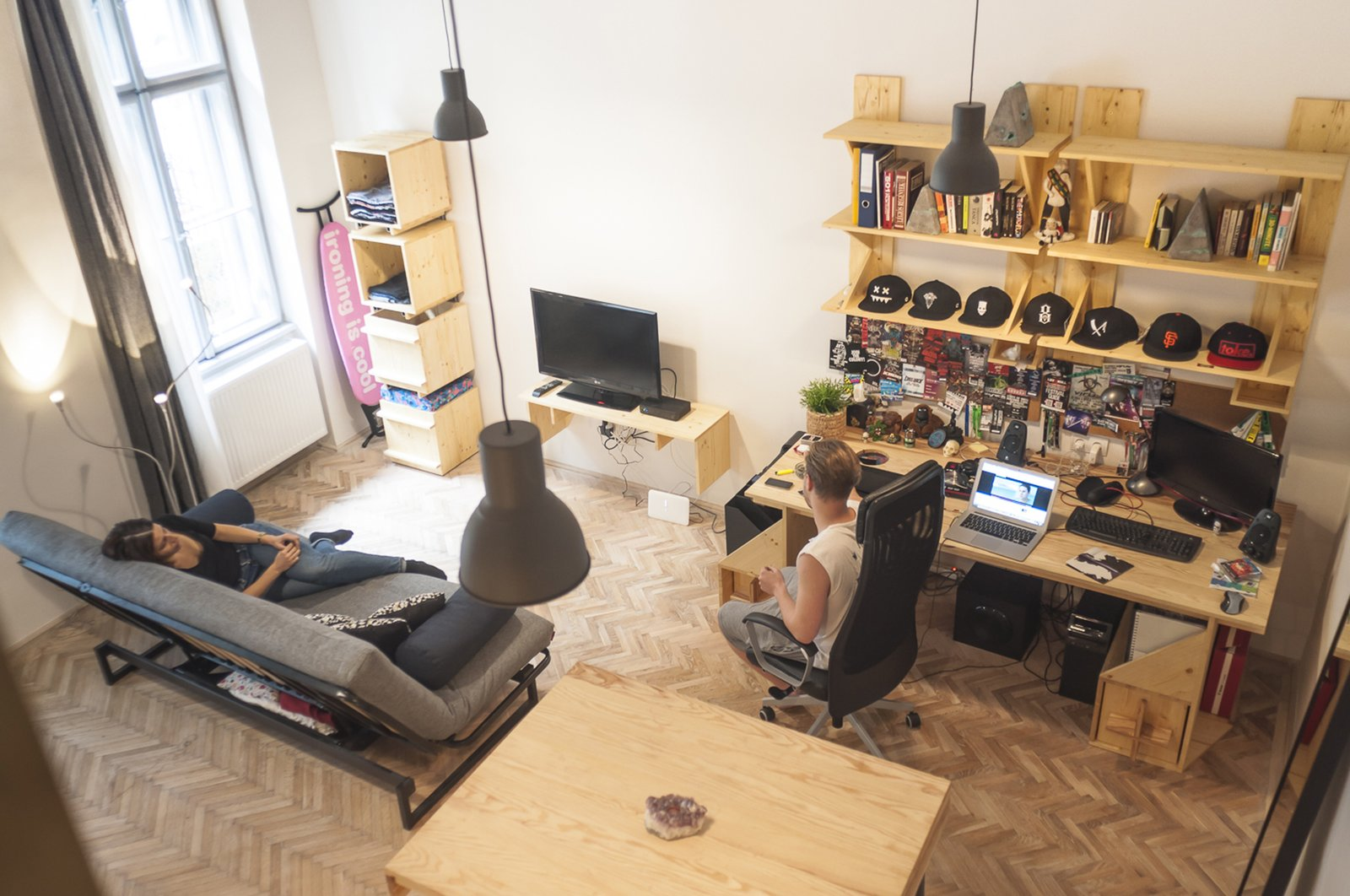 Chair, Sofa, Pendant Lighting, Bookcase, Medium Hardwood Floor, Study Room Type, Shelves, Storage, Desk, Dining Room, Bar, and Table The view from the top of Bence's lofted bedroom reveals the open atmosphere in the living room, where open storage spaces are casually filled with personal effects   Micro live:work studio by Studio Bunyik