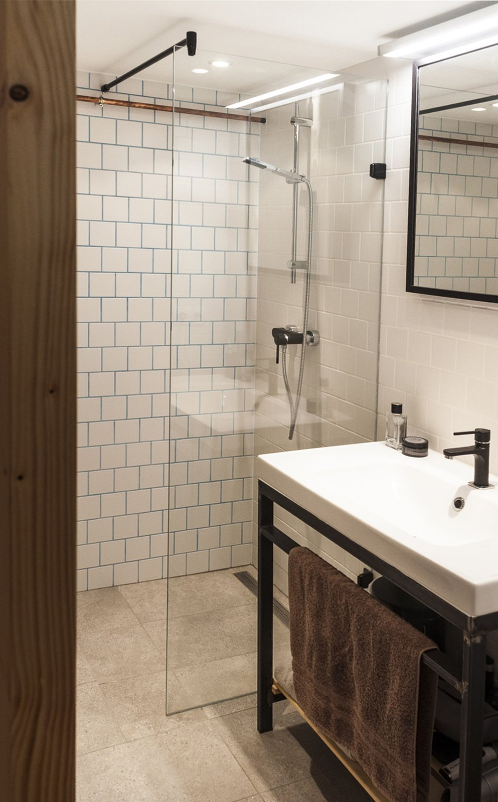 Bath Room, Metal Counter, Pedestal Sink, Open Shower, Recessed Lighting, and Ceramic Tile Wall The bathroom reflects the openness of the apartment itself, with a barely-there glass wall separating the shower  Micro live:work studio by Studio Bunyik