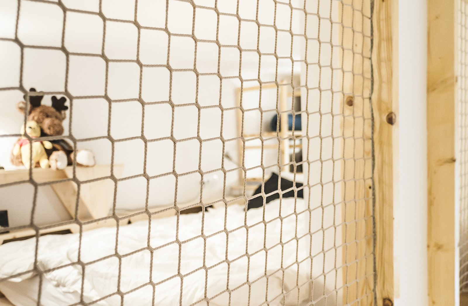 Bedroom, Light Hardwood Floor, Bed, Wall Lighting, and Shelves Netting on the bedroom loft 'windows' provide a soothing 'barrier' for those sleeping upstairs without completely closing off the nook from the rest of the space  Micro live:work studio by Studio Bunyik