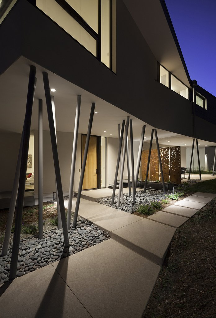 Outdoor, Hardscapes, Stone Patio, Porch, Deck, Side Yard, Metal Fences, Wall, Walkways, and Grass An array of columns partially support the second floor  6th Street by Arch11
