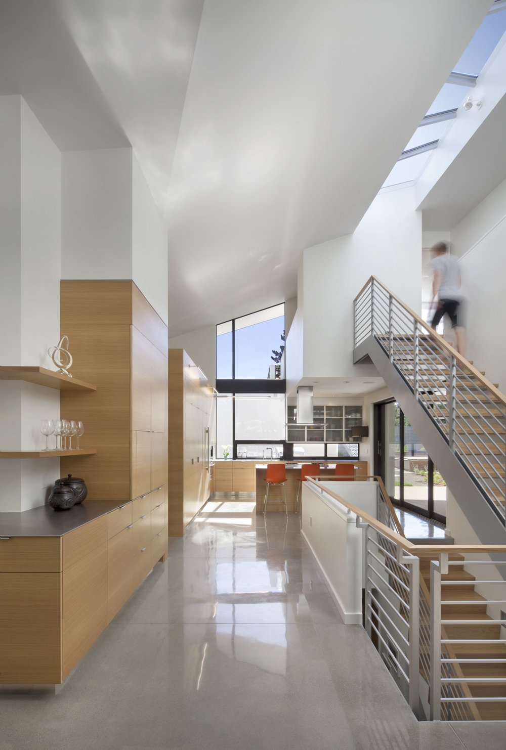 Staircase, Metal Railing, Wood Tread, and Wood Railing Minimalist design with views to every corner of the house. Vitra Hal stools in the kitchen from Design Within Reach  6th Street by Arch11
