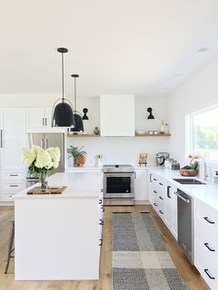 This kitchen features IKEA cabinet bases with Semihandmade fronts painted Dunn Edwards White. The lights by Rejuvenation and Kitchen Aid appliances make this the perfect space for entertaining.