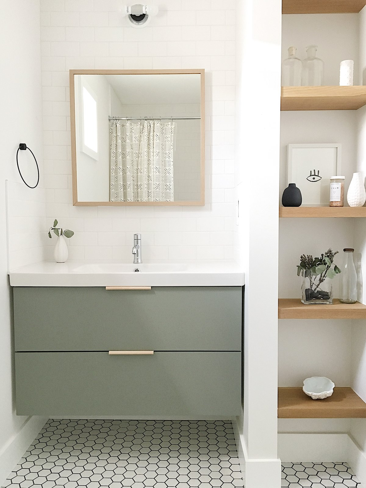Bath Room, Wall Lighting, Porcelain Tile Floor, and Subway Tile Wall The guest bathroom utilizes a simple Ikea vanity custom painted to the perfect shade of green and features leather hardware from the Australian company Made Measure.  Best Photos from The Simply Simple Home