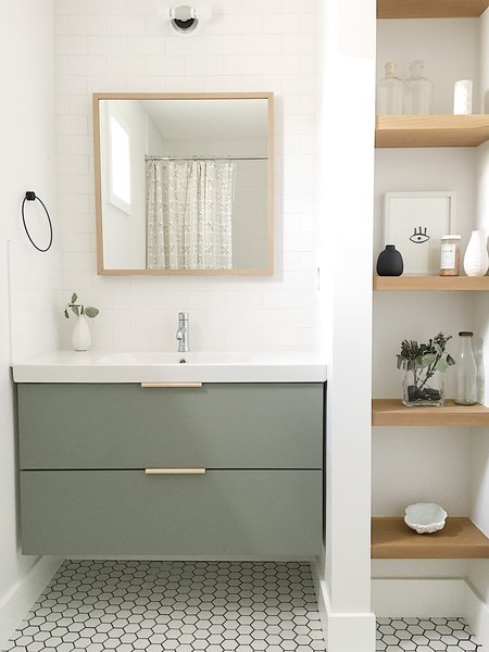Bath Room, Wall Lighting, Porcelain Tile Floor, and Subway Tile Wall The guest bathroom utilizes a simple Ikea vanity custom painted to the perfect shade of green and features leather hardware from the Australian company Made Measure.  The Simply Simple Home by Kelsey Johnston