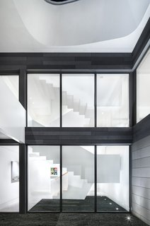 "The home is organized around a central, three-story staircase constructed of 5/8"" thick plate steel. The stair acts as a hingepoint for the various programs, with rooms and hallways unfolding from it on every floor."