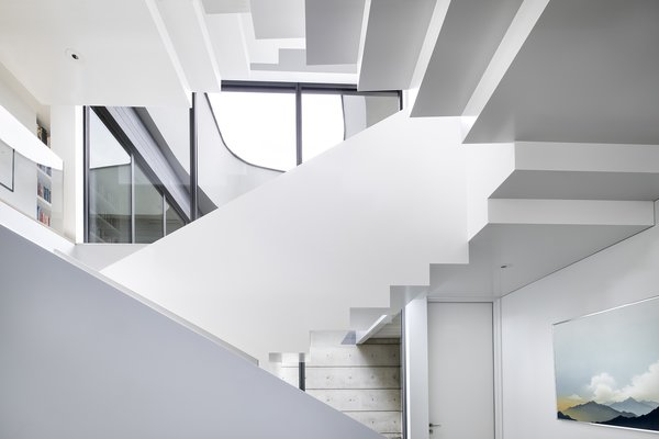 """Assembled from 5/8"""" thick plate steel with white oak treads, the staircase took eight months to fabricate, assemble, and paint."""