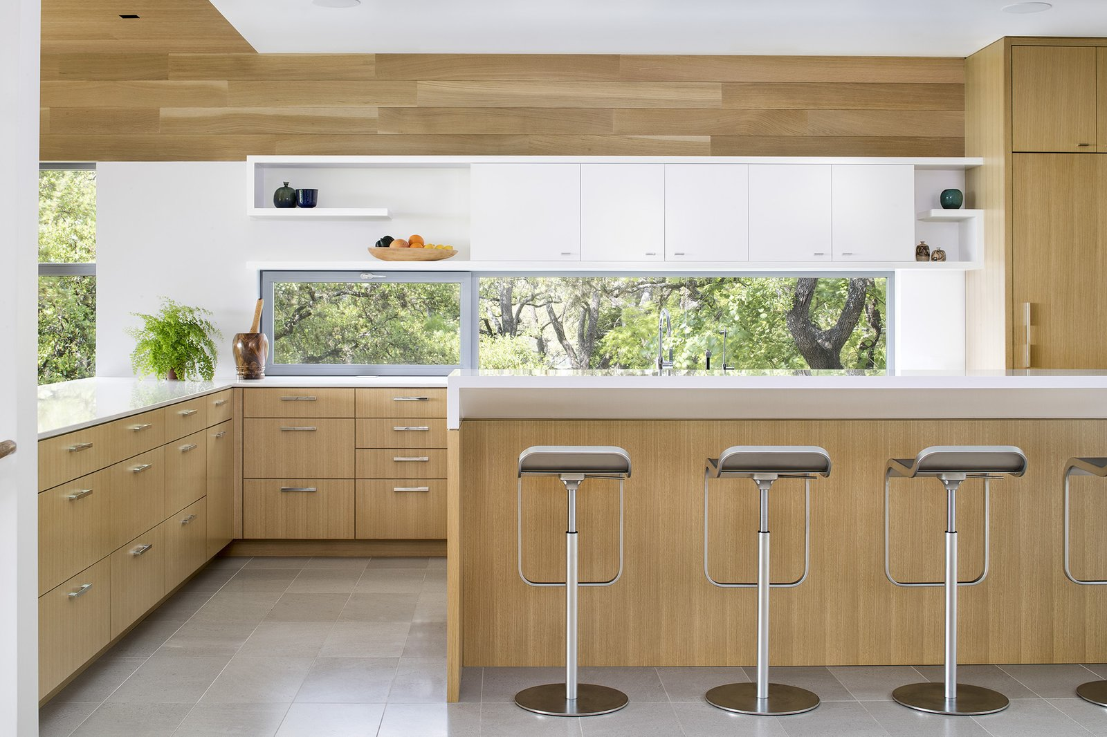 Kitchen, Recessed, Undermount, Wood, Porcelain Tile, Open, Ceiling, White, and Engineered Quartz The bright, airy kitchen combines warm white oak millwork with crisp white solid surface accents. The sink is highlighted by a glass backsplash with an operable window, while a bar-height counter at the peninsula encourages guests to congregate in the heart of the home.  Best Kitchen Ceiling Undermount White Porcelain Tile Photos from Vista Residence
