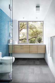 Finishes such as exposed concrete and playful tile accents denote the more laid-back, intimate atmosphere.