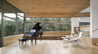 A deep bench below the windows extends the length of the space, providing additional seating. In addition to large parties, the living room also plays to host music recitals. Acoustic wood ceiling panels enhance the sound quality and provide visual warmth. Built-in benches and steps allow guests to find a comfortable corner.