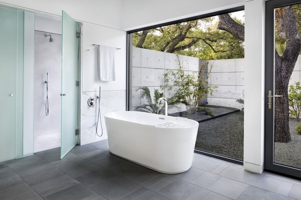 The theme of bringing the outdoors in continues in the master bathroom, which opens up to a private garden encircled by concrete walls beneath a canopy of oak trees; even the shower has direct access to the exterior. The palette of cool grays and white marble echoes the exterior finishes.