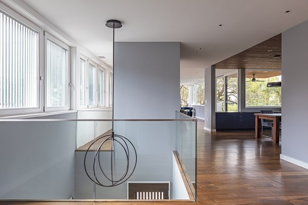 The open floor plan highlights the dichotomy between the two halves of the site: ribbon windows screen the view of the street opposite picture windows that frame the treetops and lake.