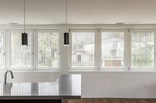 The main level houses the kitchen, dining, and living spaces, tied together by a continuous wooden wainscot whose series of half-round profiles echoes the design of the conduit screen outside.