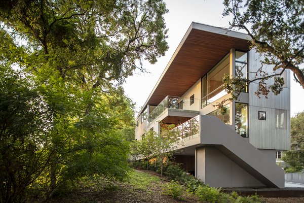 In contrast to the street façade, with its ribbon windows and metal screen, the rear of the house opens up to the natural landscape and views of downtown Austin via large windows and cantilevered terraces.