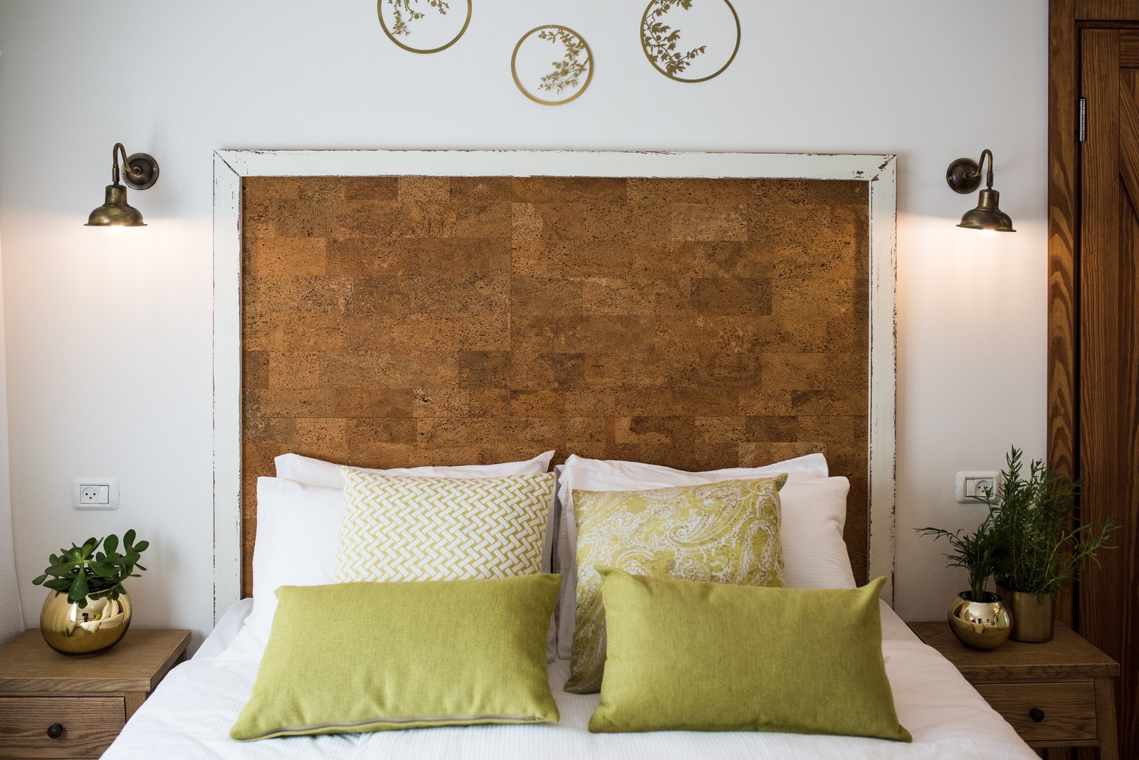 Bedroom, Bed, Wall Lighting, and Night Stands The headboard is made from cork board and painted wood  Photo 6 of 9 in A Crash Course on Cork: The Eco-Friendly Material That's Popping Up Everywhere from Golden apple guest rooms