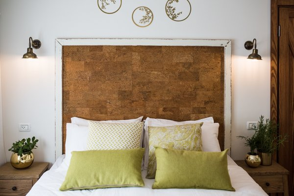 The headboard is made from cork board and painted wood