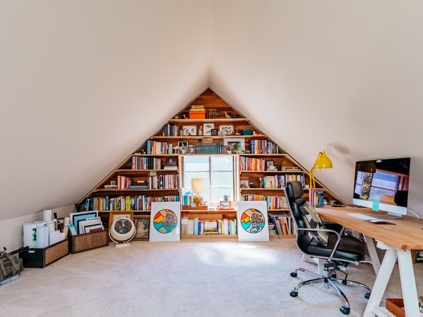 Upstairs attics and dormers are great home office ideas for small spaces. This unique home office design layout serves as both a small office and workout room for San Francisco–based knot artist Windy Chien. It also features clever storage space for the couple's voluminous collection of books.