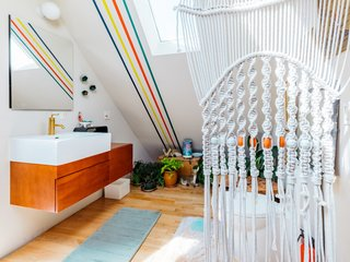 Chien's bathroom upstairs maintains the same stripes as well as an array of plants and porcelain deer nestled in the foliage.