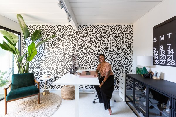 This double A-frame Eichler was renovated by Phoenix–based Mackenzie Collier Interiors. Joanne Encarnacion's office is located in the atrium, on the opposite side of her husband's. Graphic bursts of black and white are complemented by greenery and positive affirmations.