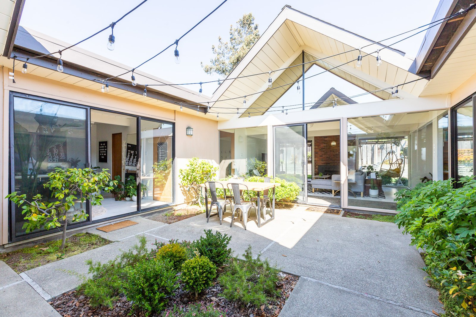 Outdoor, Trees, Concrete Patio, Porch, Deck, Shrubs, Hanging Lighting, and Small Patio, Porch, Deck The atrium, one of the main distinguishing features of Eichler homes, connects the two A-frames.  Photo 2 of 16 in Wellness Guru Joanne Encarnacion's Blissful A-Frame Eichler